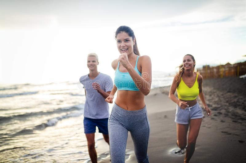Group of athletes running on ocean front. Friends in sportswear training together outdoors. stock photography