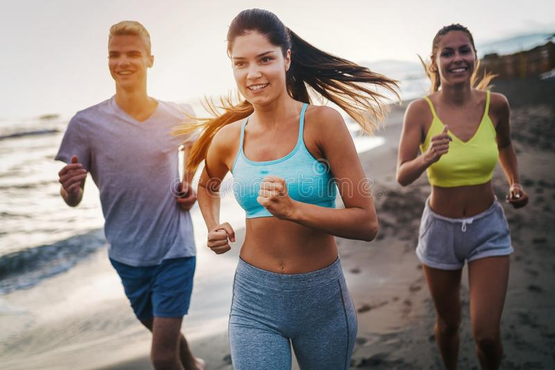 Group of athletes running on ocean front. Friends in sportswear training together outdoors. stock photo