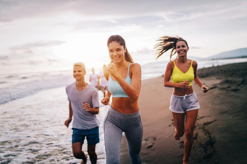 Group of athletes running on ocean front. Friends in sportswear training together outdoors. royalty free stock images