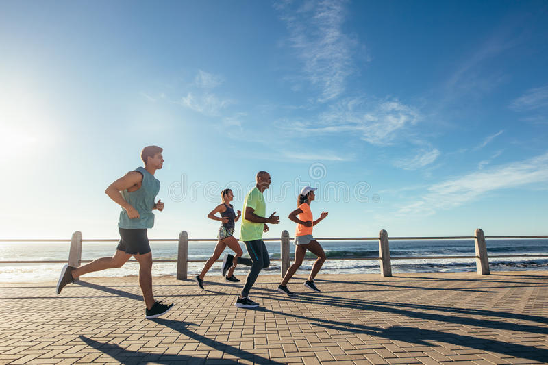 Group of athletes running on ocean front royalty free stock photos