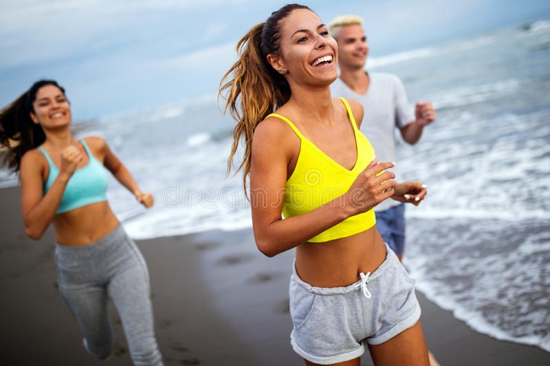 Group of athletes running on ocean front. Friends in sportswear training together outdoors. stock images