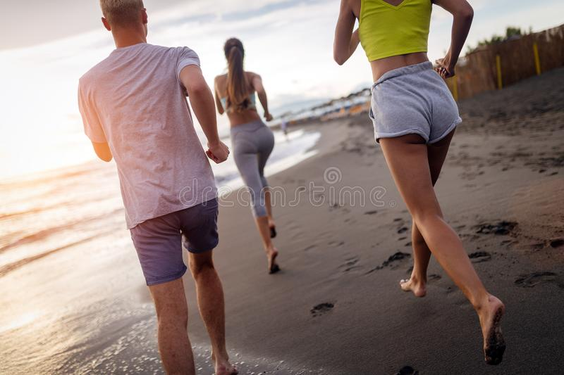 Group of athletes running on ocean front. Friends in sportswear training together outdoors. royalty free stock photography