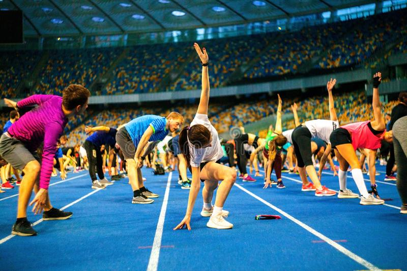Group athletes training for better hamstring flexibility at the stadium. royalty free stock photos