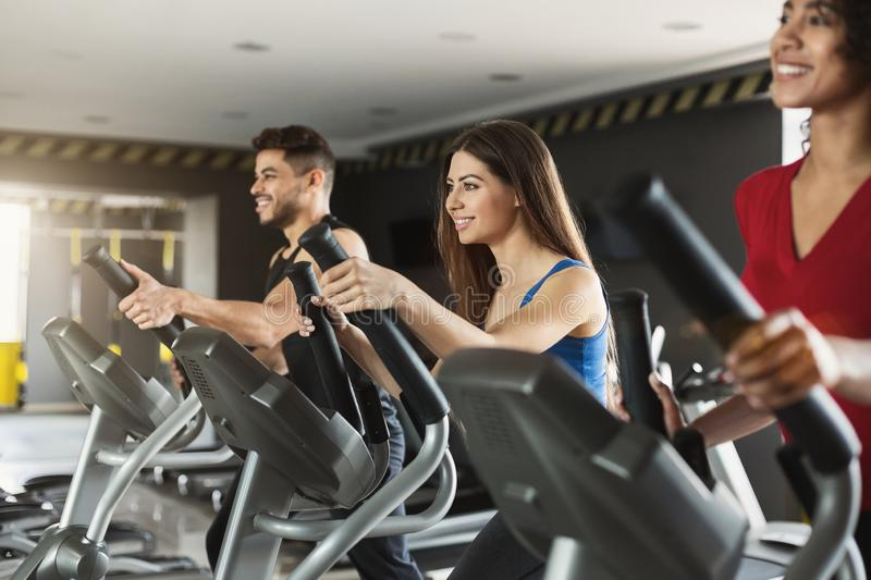 Group of athletes using cross-trainers in sport club stock photos