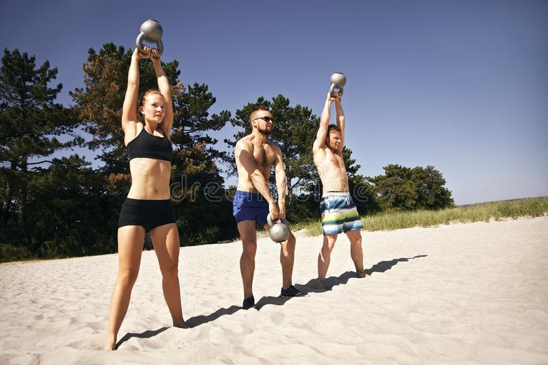 Group of athletes working out with kettle bell on beach. Group of athletes swinging a kettle bell over their head on beach. Young people doing crossfit workout royalty free stock images