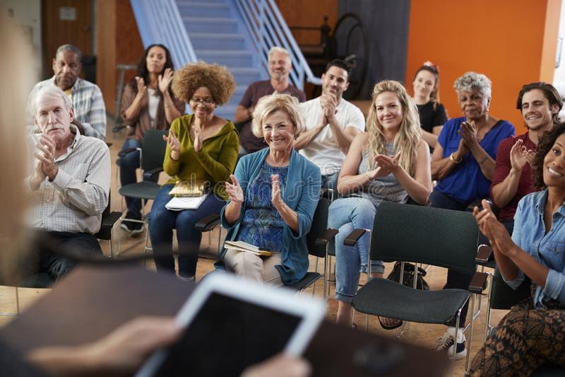 Group Attending Neighborhood Meeting Applauding Speaker In Community Center stock photos
