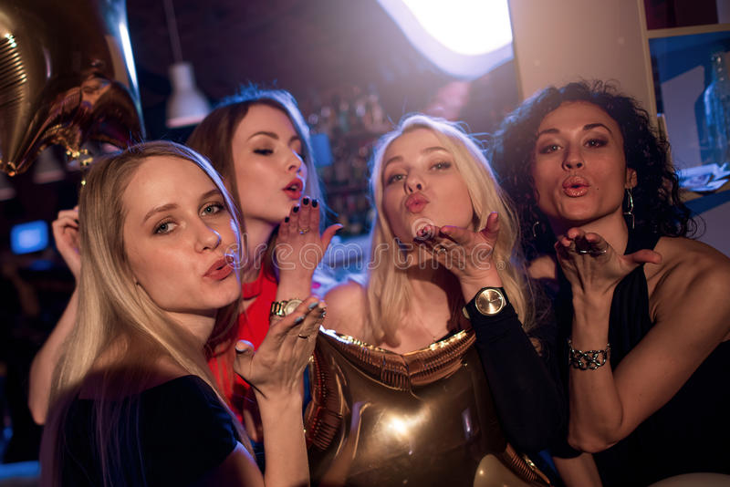 Group of attractive gorgeous girls blowing kisses looking at camera in nightclub.  royalty free stock photos