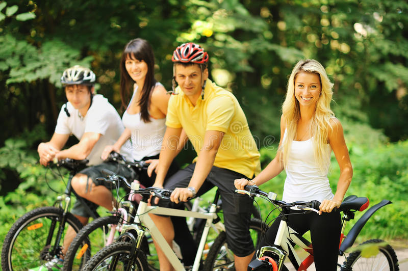 Group of attractive happy people on bicycles in the countryside.  stock image