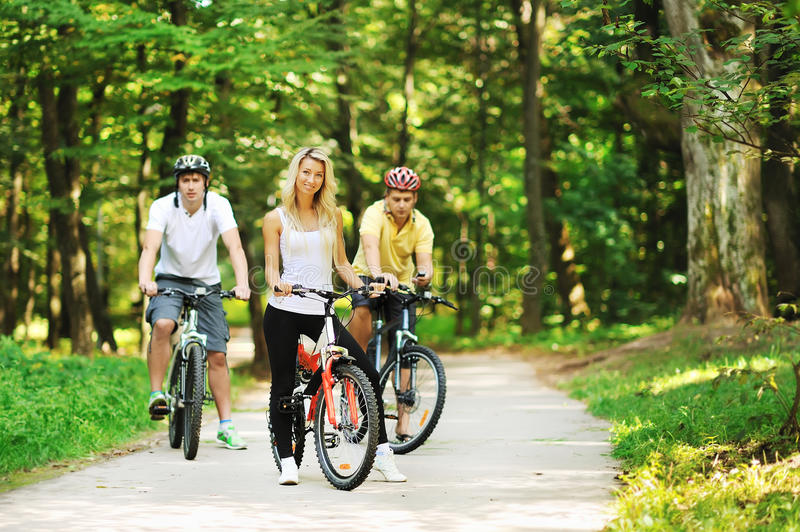 Group of attractive happy people on bicycles in the countryside.  stock images