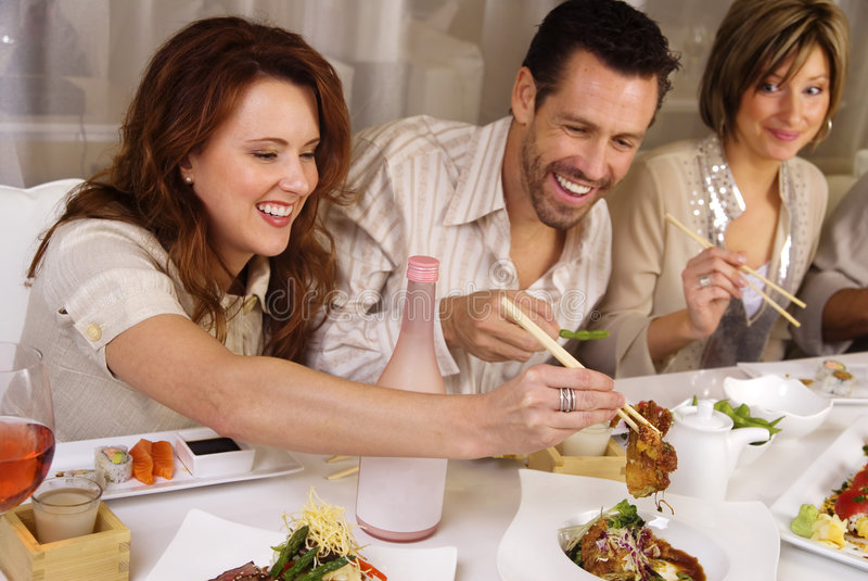 Group of attractive people eating and socializing. At a restaurant. The expressions caught on camera are genuine moments of fun, playing with chopticks royalty free stock photo