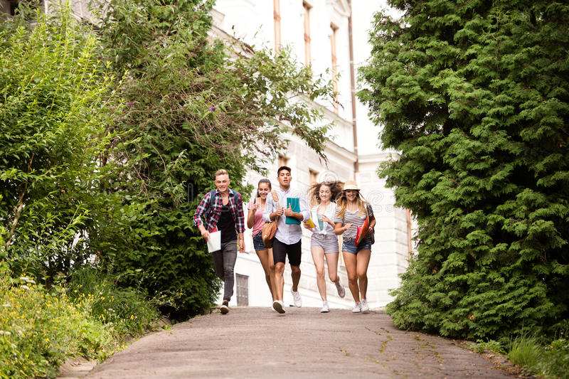 Group of attractive teenage students running from university. stock photos