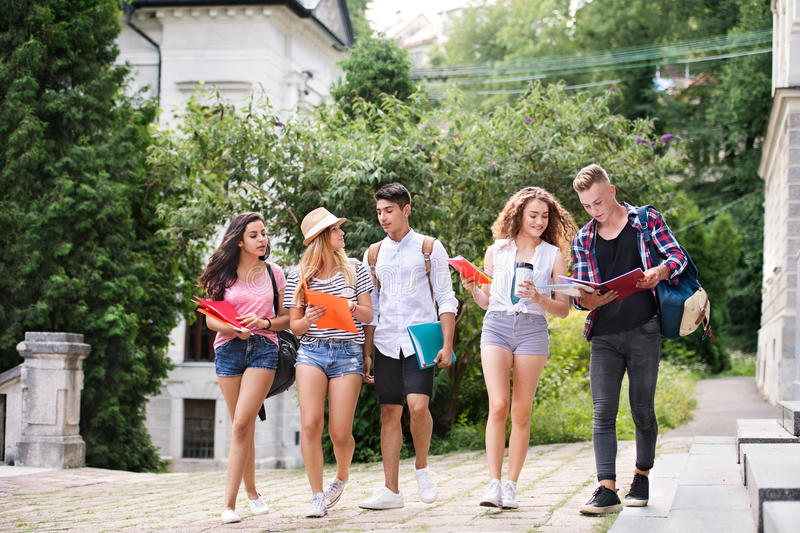 Group of attractive teenage students walking to university. stock photography
