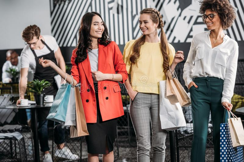 Group of attractive young women with shopping bags. In cafe stock photography
