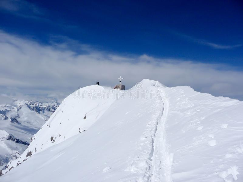 Back country skiers and mountain climbers near a high alpine summit cross with a narrow and exposed ridge leading towards them stock image