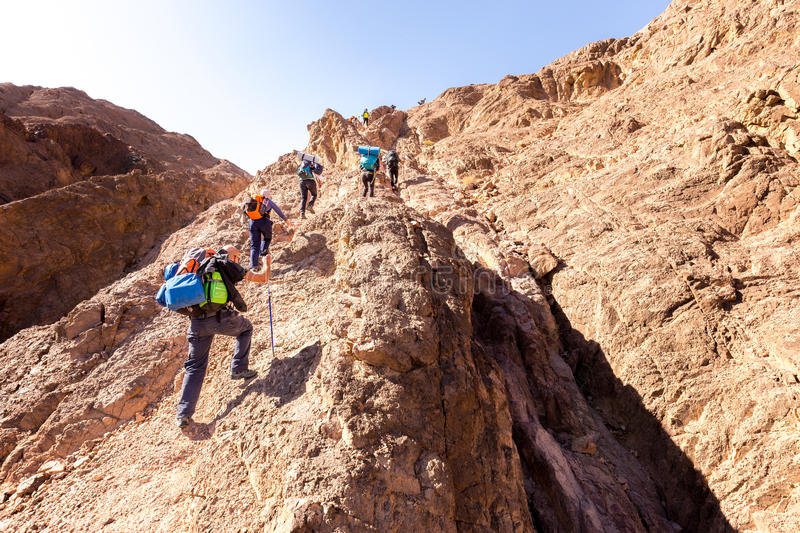 Group backpackers ascending climbing desert mountain trail lifestyle. stock photography