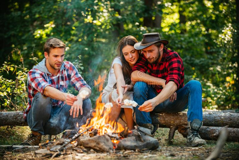 Group of backpackers relaxing near campfire. Friends spend leisure weekend forest nature background. Tourists relaxing royalty free stock photos