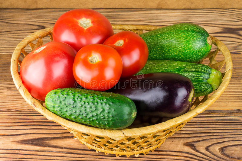 Group of backyard vegetables in wicker basket on wooden background. stock photos