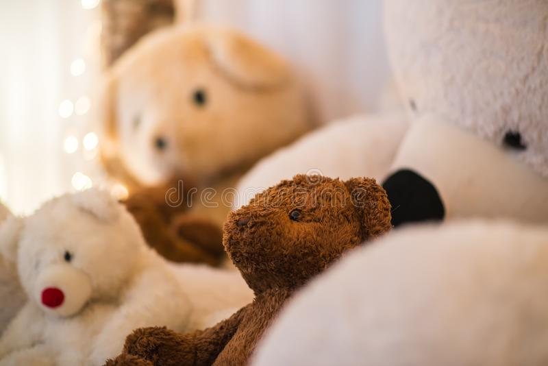 Closeup brown and white teddy bears lay with christmas lights blurred in the background. Cozy winter night stock photo
