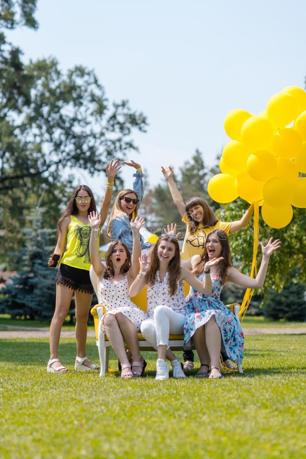 Group of beautiful girls laughing on the lawn stock image