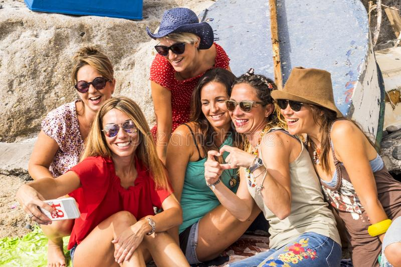 Group of beautiful young females friends having fun together outdoor in leisure activity doing a selfie with a smartphone. stock photo