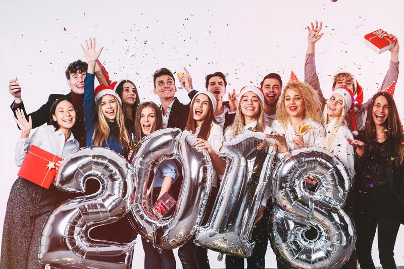 Group of beautiful young people in Santa hats holding silver colored number balloons and colorful confetti. New 2018 year party royalty free stock image