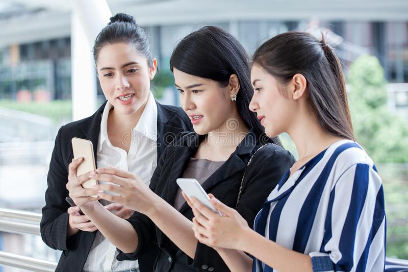 group of beautiful young women friends using a smart phone and laughing outdoors .three girl exciting business online of news royalty free stock photos