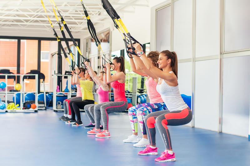 Group of beautiful young women working out on TRX. Group of beautiful young women working out on TRX and smiling royalty free stock photo