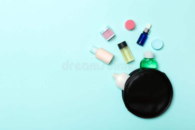 Group of beauty cream bottles dropped out of the cosmetics bag on blue background. Space for your design. Top view of skincare royalty free stock photo