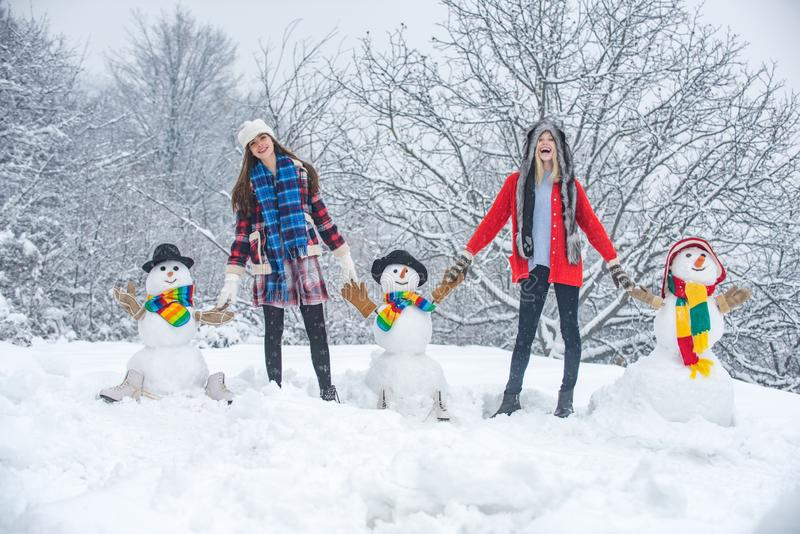 Group of Beauty Winter Girls with snowman. Students party and Christmas celebration. Two Joyful Beauty young women royalty free stock images