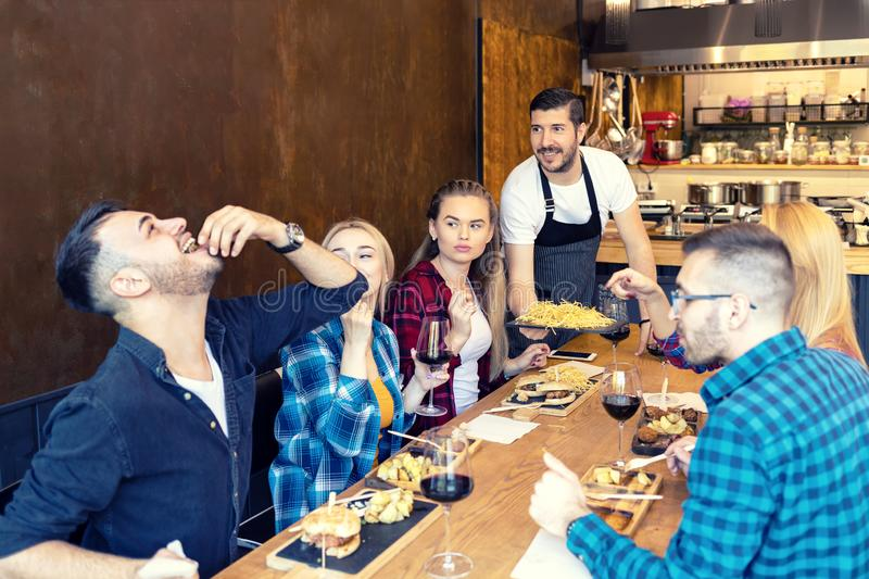 Group of best friends eating tasty food in small restaurant while happy owner serving them. Young people enjoying time together at trendy pub drinking red wine stock images