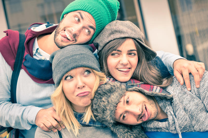 Group of best friends taking selfie outdoors with funny face. Expression and fashion clothes - Happy friendship concept with young hipster people having fun stock photos