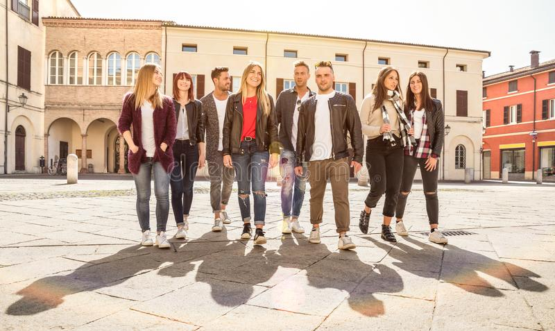 Group of best friends walking and talking in city center - Tourist guys and girls having fun around old town streets - University royalty free stock photography