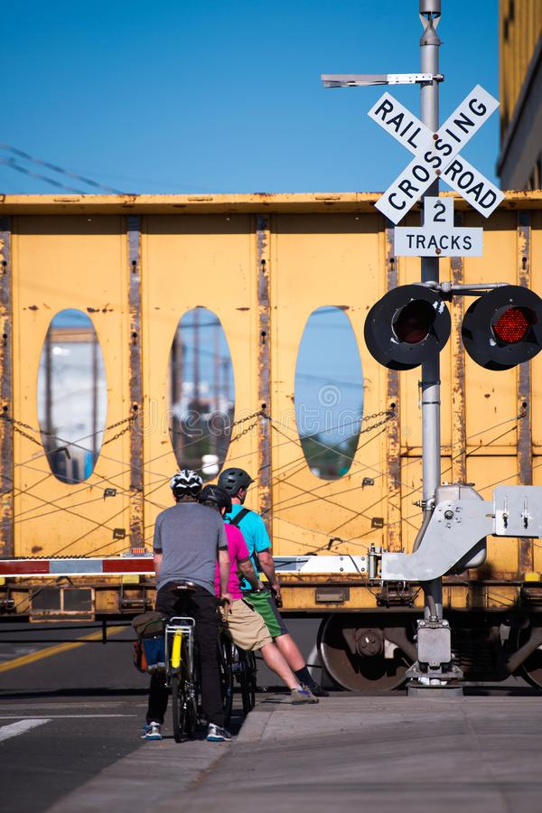 Group of bikers are waiting for the train to pass and the barrie royalty free stock image