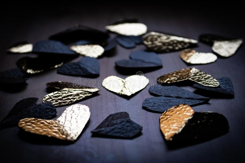Group of black and golden foil hearts on the wooden table stock image
