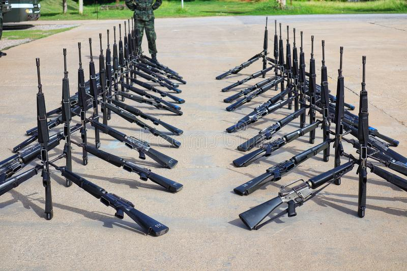 The group of black rifles lay on the cement floor to organize military combat concepts. Outdoor stock photo