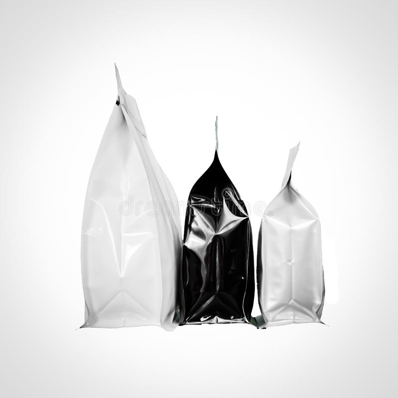 Group of black and white square flat bottom coffee plastic pouches  with zipper  filled with coffee beans on white background royalty free stock photography