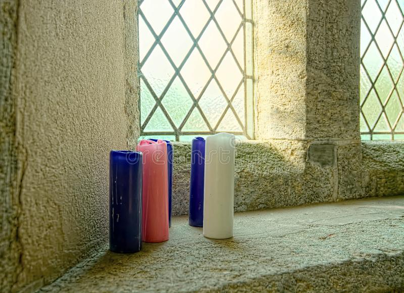 Ancient church interior. Colored candles. A group of blue and pink candles on a window ledge in an ancient church as the light floods in from the leaded windows royalty free stock photo