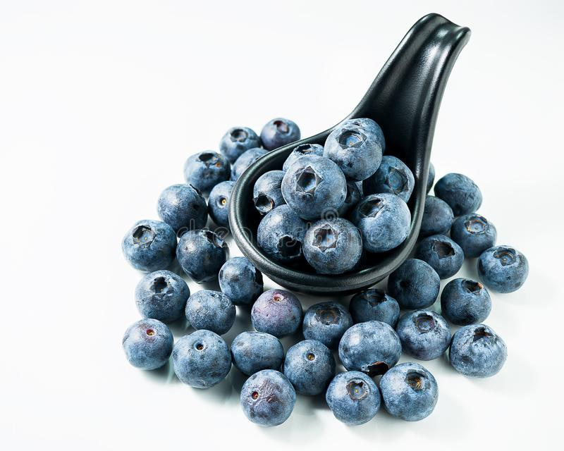 Group of blueberries on black spoon isolated white background royalty free stock image