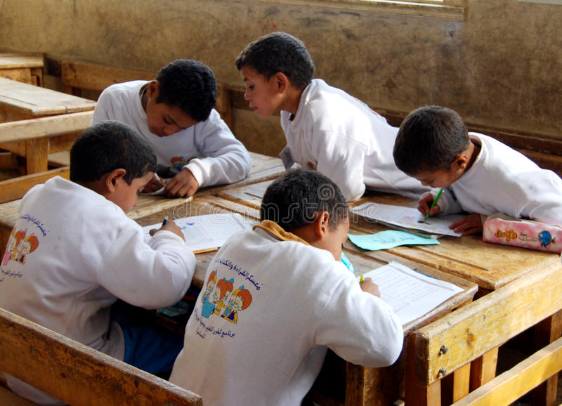 Group of boys in class writing homework sitting on desk royalty free stock images