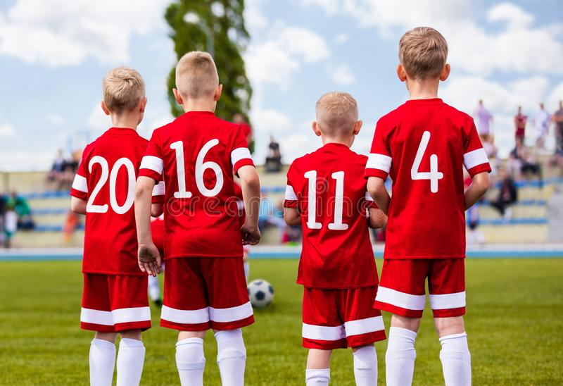 Group of boys football soccer players standing together on green stock photos