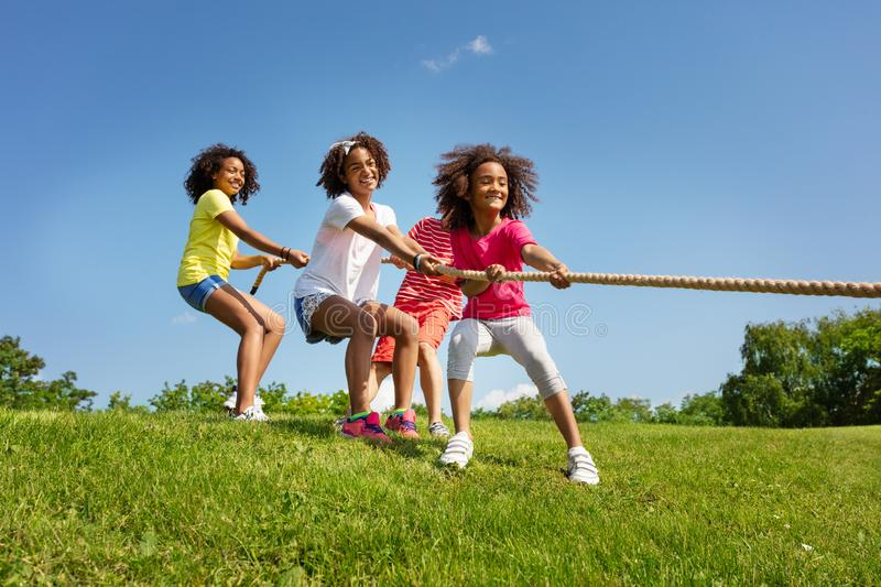 Group of boys and girls play pulling cord game. In park lawn during summer camp stock image