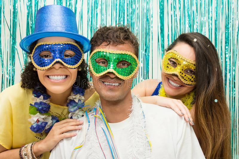 Group of Brazilian friends wearing Carnaval costume. Masked revelers pose for the photo.. Multi ethnic group of friends is wearing Carnaval masks. Happiness and stock images