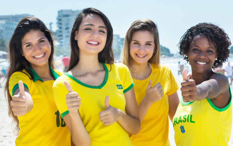 Group of brazilian soccer fans showing thumbs outdoor in the city. In the summer royalty free stock image