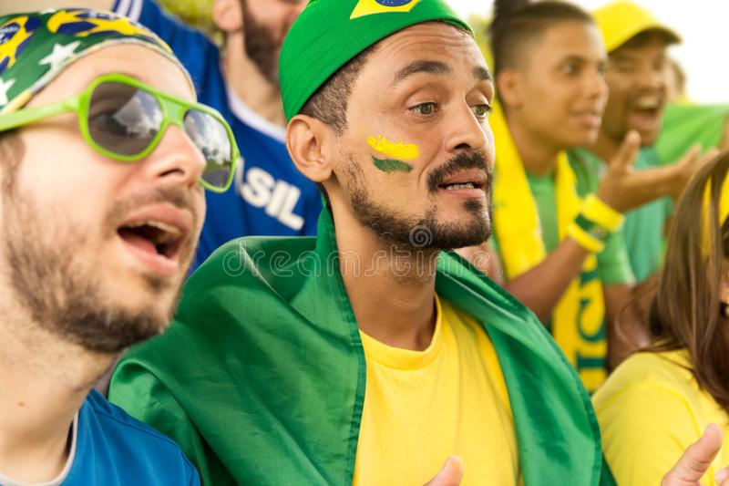 Friends from Brazil watching football match. Group of brazilian supporters cheering at stadium. Emotions portrait. Surprised expression, complain, fault stock image