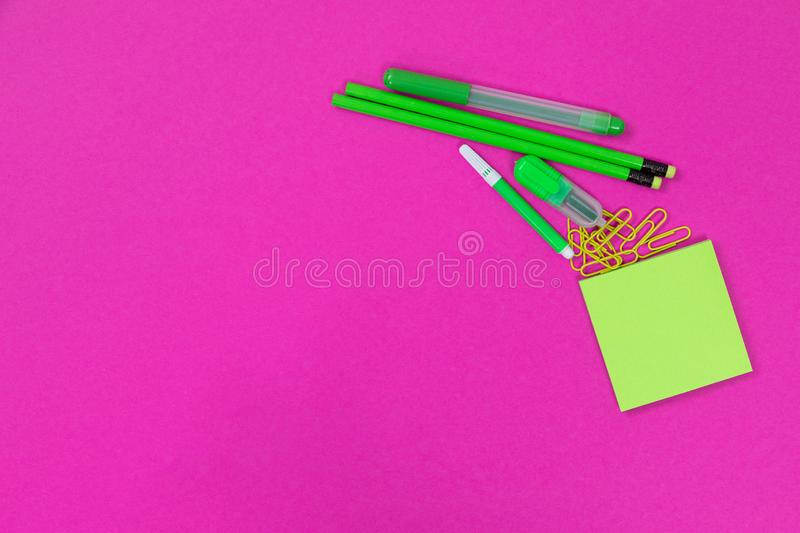 A group of bright green office requisites is lying in the upper right corner on pink background isolated royalty free stock photography