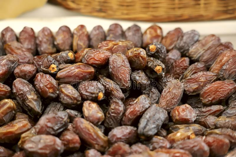 A group of brown dried dates lie in rows on the counter on the market. royalty free stock image