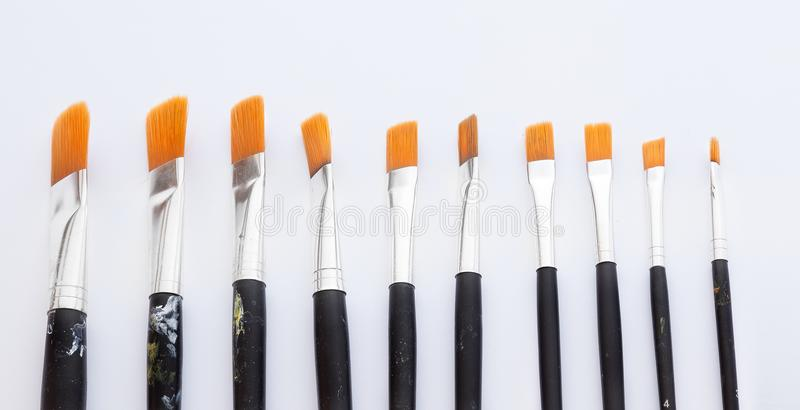 Brushes aligned to represent choices in art. A group of brushes of different sizes and a bit dirty aligned from the biggest to the smallest, fine art brushes royalty free stock photo