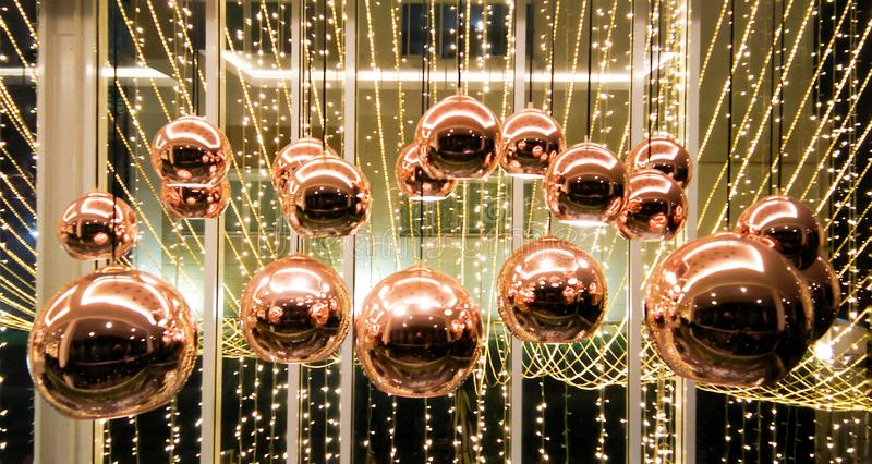 Shiny copper sphere lamps. Group of bubble copper lamps hanging on ceil and decorated by line of little warm white electricity light look so beautiful and royalty free stock image