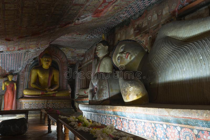 Group of Buddha statues in cave buddhist temple. With bright painted murals on walls and ceiling in Dambulla Golden temple in Sri Lanka royalty free stock photo
