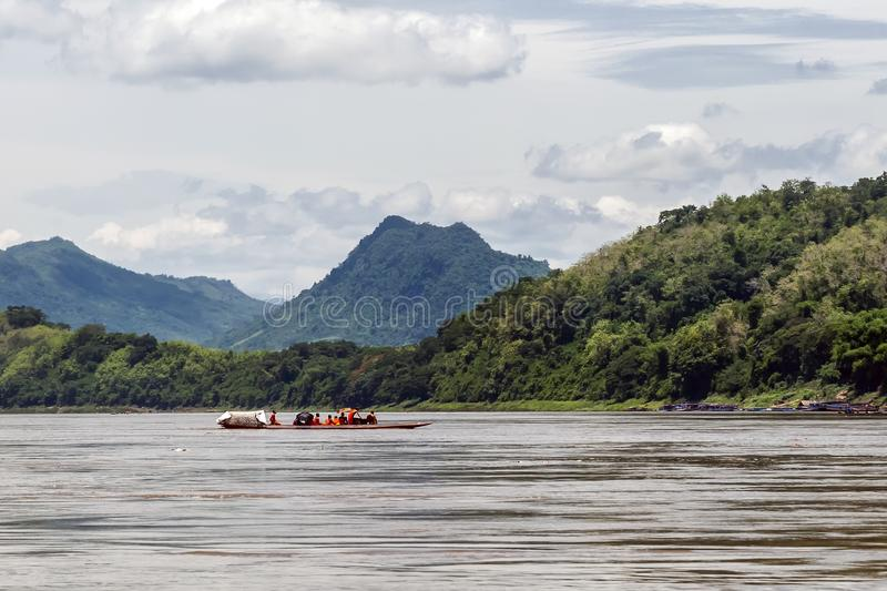Group of Buddhist monks navigate the Mekong River with a long tail boat in Luang Prabang, Laos royalty free stock images